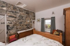 Stone walls in the guest bedroom at maumeen cottage in Galway